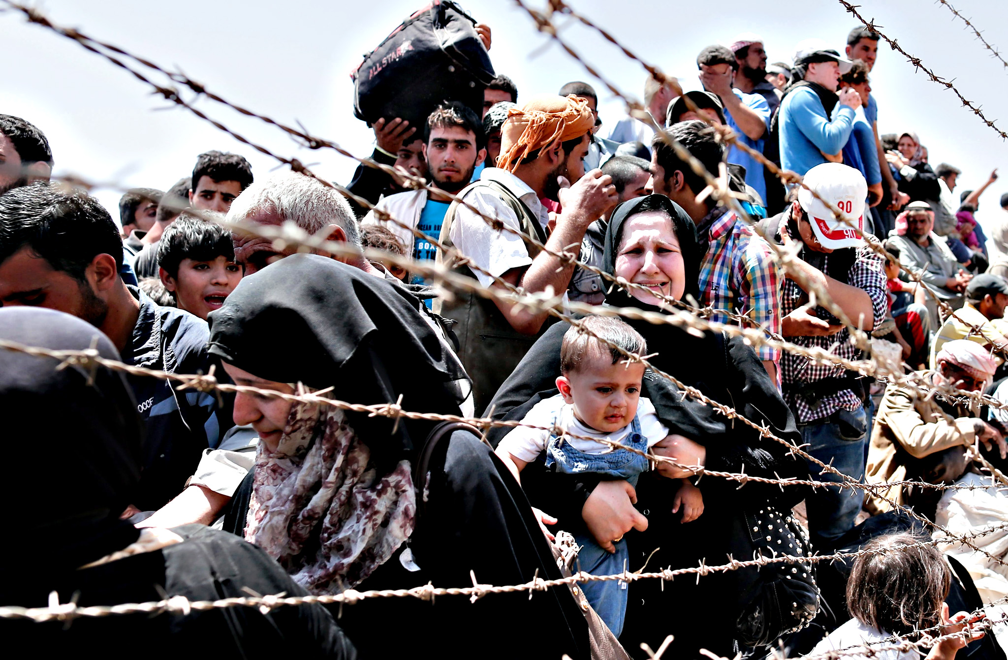 Syrian refugees at Turkey-Syria border...epa04791762 A picture taken from the Turkish side of the border between Turkey and Syria shows Syrian refugees waiting on the Syrian side of the border crossing near Akcakale, Sanliurfa province, south-eastern Turkey, 10 June 2015. More than 320,000 people are likely to have been killed in Syria's civil war, the Britain-based Syrian Observatory for Human Rights monitoring group said on 09 June. The organization said said it had been able to document the deaths of 230,618 people, including 69,494 civilians of whom more than 7,000 were children. The crisis in Syria started in March 2011 with peaceful demonstrations calling for more freedom from the repressive al-Assad regime, but quickly degenerated into violence after deadly crackdowns by security forces.  EPA/SEDAT SUNA